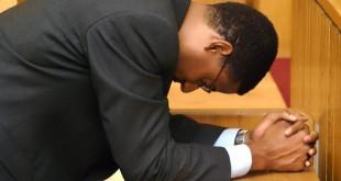 Side profile of a businessman praying --- Image by © Karen Lim/DK Stock/Corbis